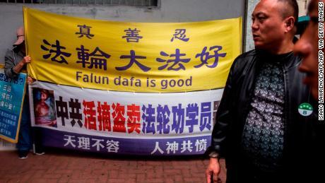 Un activiste du Falun Gong (à gauche) tient une pancarte à côté des hommes d'un groupe de touristes chinois et postaux dans le quartier de Kowloon à Hong Kong le 6 janvier 2019.