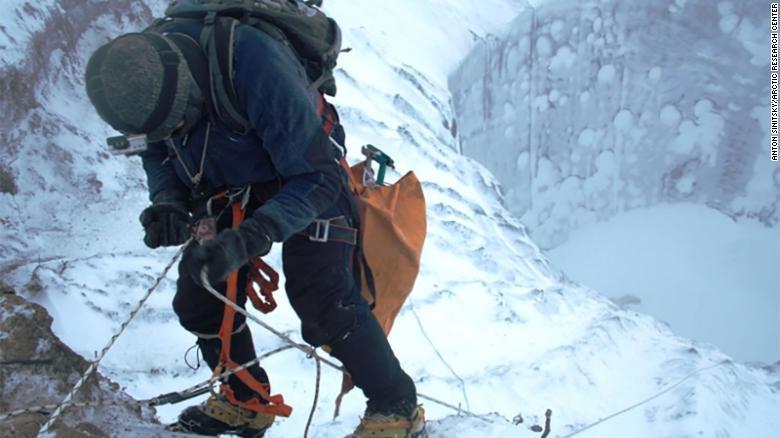 A researcher climbs down the Erkuta crater.