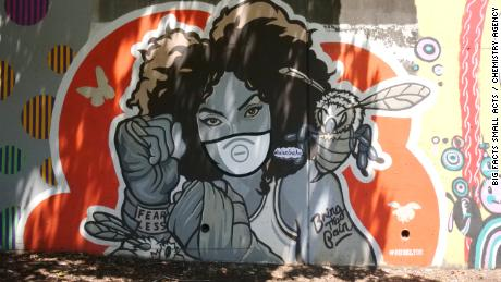 Artist Dubelyoo covered his mural of a woman boxer with a vinyl mask in Atlanta's Cabbagetown neighborhood as a visual reminder to wear a mask to fight Covid-19.