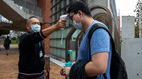 Taiwanese students get their temperature checked as they enter the Taipei American school on March 18, 2020 in Taipei, Taiwan.