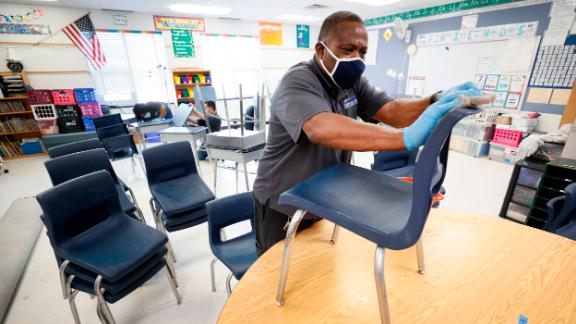Des Moines Public Schools custodian Tracy Harris cleans chairs in a classroom at Brubaker Elementary School, on Wednesday, July 8, 2020, in Des Moines, Iowa.