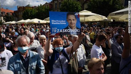 Un partisan de Rafal Trzaskowski tient une bannière alors que le maire de Varsovie prononce un discours lors d'un rassemblement électoral le 7 juillet à Gniezno, en Pologne.