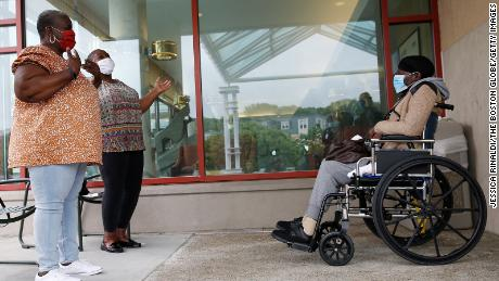 (From left) Ina Barbosa, of Attleboro, Mass., and Kimberley Vann-Lites, of Norton, Mass., visit with their mother, Mary Vann, age 85, in person for the first time since the coronavirus pandemic shut down visits to Hebrew Rehabilitation Center in Boston's Roslindale, on June 11, 2020.