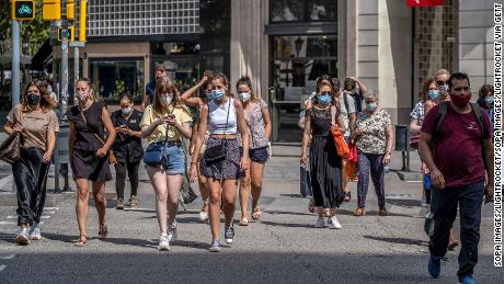 People wear face masks in Barcelona, Spain, where those who do not do so in a public room are fined 100 euros.