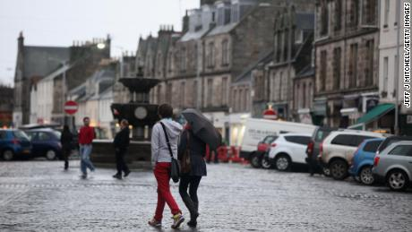 People walk past a fountain in St Andrews, Scotland.