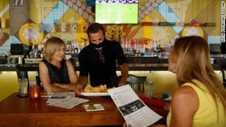 Jorge Hernandez serves a plate of chips to Lora Renz, left, and Amy Lilly at the Tequila Museo Mayahuel restaurant in Sacramento, Calif., Wednesday, July 1, 2020. California Gov. Gavin Newsom has ordered a three-week closure of bars, indoor dining and indoor operations of several other types of businesses in 18 counties, including Sacramento, as the state deals with increasing coronavirus cases and hospitalizations. (AP Photo/Rich Pedroncelli)