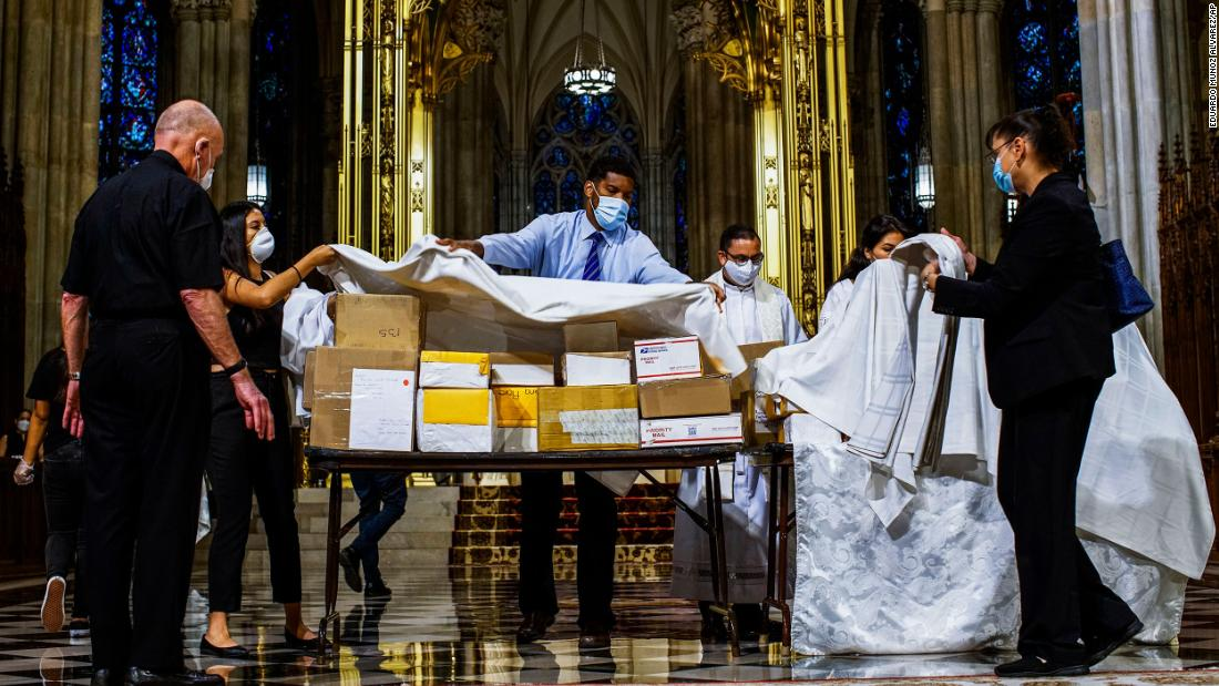 The boxed cremated remains of Mexicans who died from Covid-19 are covered before a service at  St. Patrick's Cathedral in New York on July 11. The ashes were blessed before they were repatriated to Mexico.