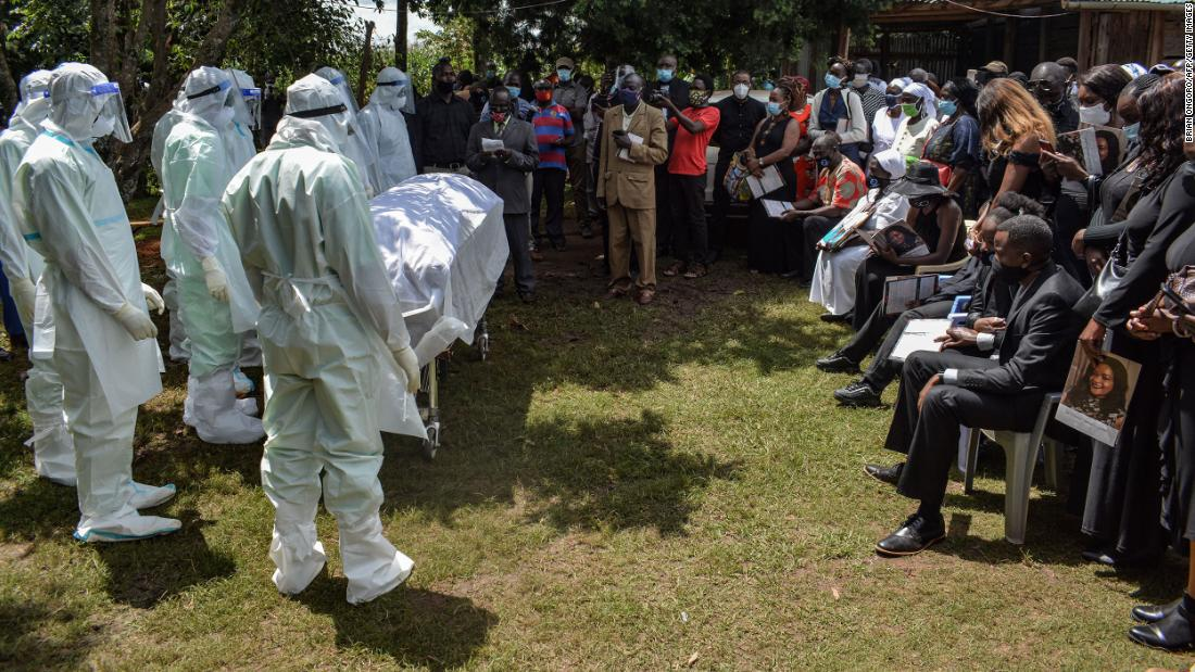 Members of the Bungoma County Isolation Team stand by the coffin of Dr. Doreen Lugaliki during her funeral in Ndalu, Kenya, on July 13. Lugaliki, 39, died from complications related to the novel coronavirus.