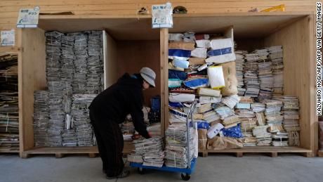 A worker sorts newspapers and magazines for recycling at a waste center in the city of Kamikatsu, Tokushima Prefecture.