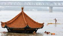 Locuitorii înoată în fața unui pavilion lângă râu scufundat de râul Yangtze inundat în Wuhan, în provincia Hubei din China, la 8 iulie.