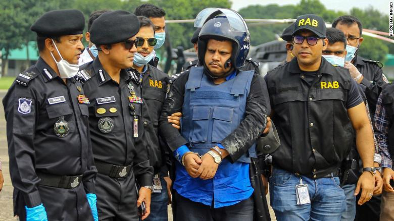 Bangladeshi security personnel escort Mohammad Shahed (center) in Dhaka following his arrest.