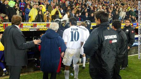 Figo leaves the pitch as play was suspended during Barcelona's match against Real.