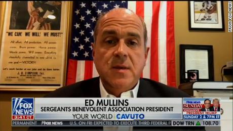Ed Mullins during an appearance on Fox News Friday. A coffee mug with the logo of QAnon sits above his left shoulder in the bottom right of the photo.