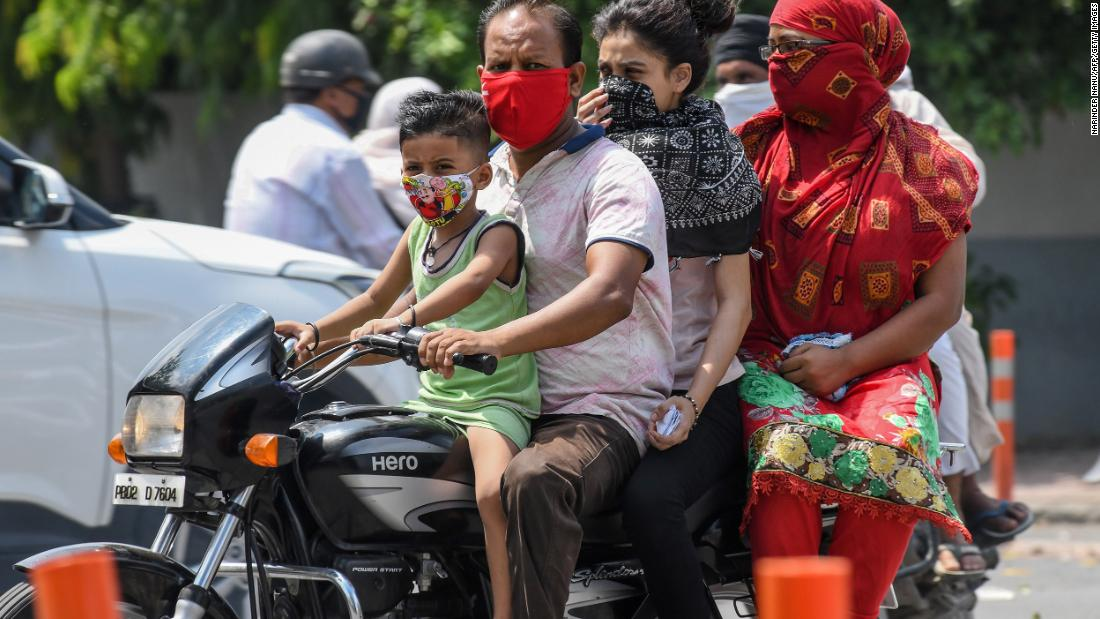 <strong>India:</strong> A boy and a man wear face masks while riding with their family on a motorbike in Amritsar on July 8.