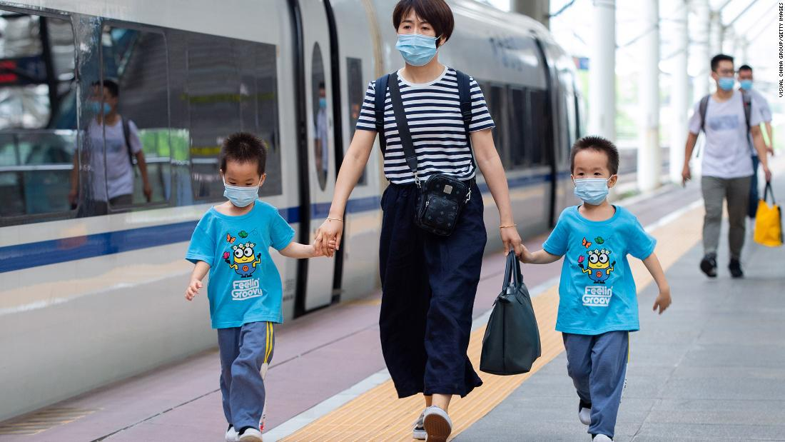 <strong>China: </strong>Children wearing face masks prepare to board a train at Nanjing Railway Station before the three-day Dragon Boat Festival holiday on June 24, 2020.