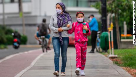 A woman walks with her daughter wearing face masks in Lima, Peru.