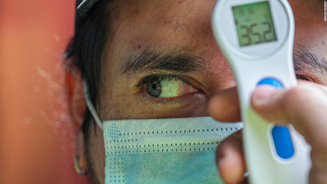 A worker measures a man's temperature before allowing him to enter La Vega market in Santiago, Chile, on July 19.