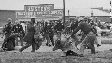 "A state trooper swings a billy club at John Lewis, right foreground, in 1965 on ""Bloody Sunday"" in Selma, Alabama."