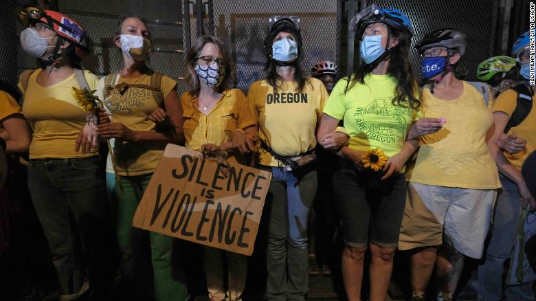 Women with interlocking arms stand with their backs against a fence blocking access to the entrance of the federal courthouse in Portland.
