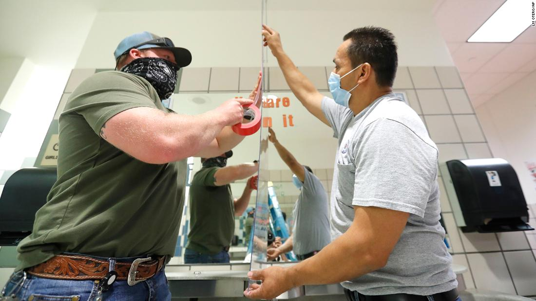School workers Matt Attaway, left, and Rogelio Ponciano install a Plexiglas barrier in a restroom at Bukhair Elementary School in Dallas on July 15.