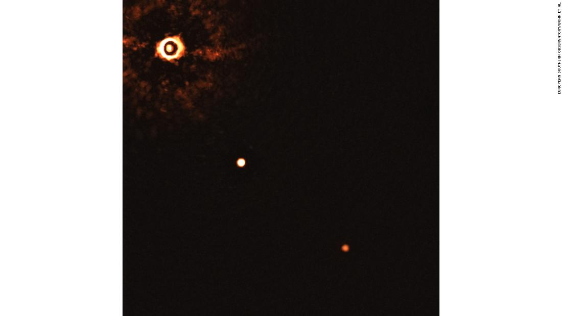 This image shows a young sun-like star being orbited by two gas giant exoplanets. It was taken by the SPHERE instrument on European Southern Observatory's Very Large Telescope. The star can be seen in the top left corner, and the planets are the two bright dots.
