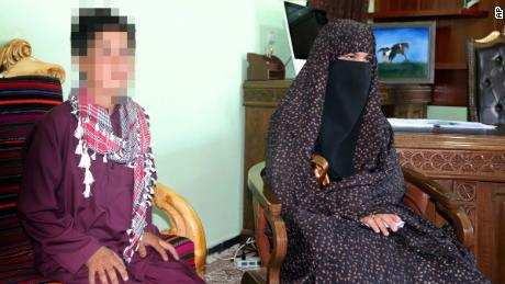 CNN has blurred part of this image to protect the identity of the subject. Qhamar and Habibullah Gul pose for photographs in the governor's office in Feroz Koh, the provincial capital of Ghor province, in western Afghanistan, Tuesday, July 21, 2020.