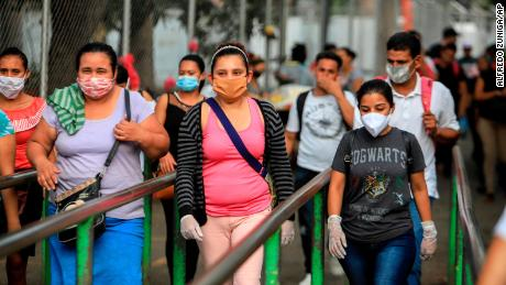 Workers wear masks as protection against the spread of coronavirus as they leave after a day's work in Managua, Nicaragua, on May 11, 2020.