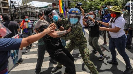 Police wearing face masks arrest protesters during a LGBTQ pride march in Manila, Philippines, Friday June 26.