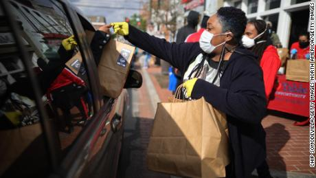 WASHINGTON, DC  - APRIL 01: Martha's Table volunteer Poet Taylor helps distribute hundreds of free hot meals donated by the Clyde's Restaurant Group to people in need during the novel coronavirus pandemic, which has forced many people out of work and unable to reach healthy food, April 01, 2020 in Washington, DC. Martha's Table, a nonprofit organization that works to help underserved communities, is extending until April 24 its COVID-19 emergency response of financial and food support for people in need, including a weekly distribution of 6,570 bags of groceries at its public food sites in Southeast Washington, DC.  (Photo by Chip Somodevilla/Getty Images)