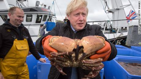 Boris Johnson holds a crab at Stromness Harbour in July 2020 in Stromness, Scotland.