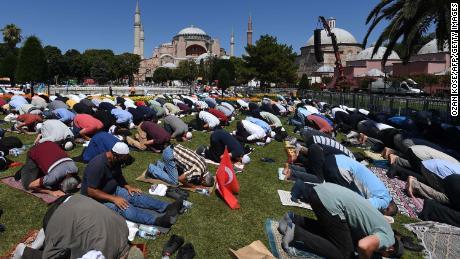 Los hombres participan en las oraciones de los viernes frente a Hagia Sophia en Estambul el 24 de julio de 2020.