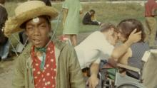 Caption:, Camper Cary Walker poses with a straw hat on, while in the background, a couple in wheelchairs shares a romantic embrace., Visual Description:, Vintage color snapshot at Camp Jened. Cary Walker, a young African American camper, squints at the camera with a bemused look, wearing a straw hat, a red shirt with white-polka dots, and an army-green jacket. He appears to have a white sticker on his forehead. Behind him, a couple sitting in wheelchairs share a romantic embrace, looking like they just kissed or are about to kiss., Alt Text:, Vintage snapshot of two campers in wheelchairs kissing while another camper squints at the camera wearing a straw hat.