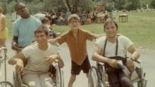 Caption:, 1968 outdoor color snapshot. Four male campers, two in wheelchairs, smile for the camera. Behind them a large group assembles in the Jened field., Visual Description:, two sitting in manual wheelchairs and two standing, smile for the camera. The boy standing in the middle has his arms on the backs of the wheelchairs to either side of him. Behind them a large group assembles in the Camp Jened field., Alt Text:, Vintage snapshot of four Jened campers, smiling for the camera.