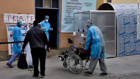 Los trabajadores de salud llevan a un paciente sospechoso de coronavirus a un hospital en La Paz el 23 de julio de 2020.