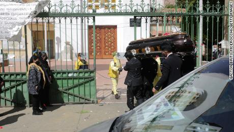 Los directores de funerarias llevan un ataúd durante un funeral en La Paz.