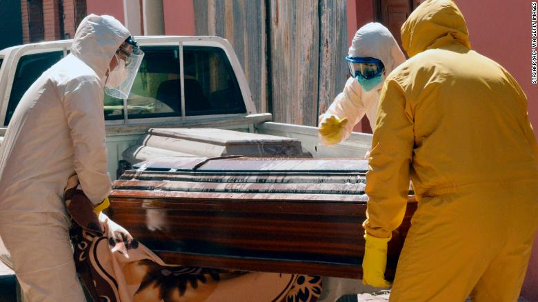 Medical workers carry a coffin containing a coronavirus victim in Cochabamba.