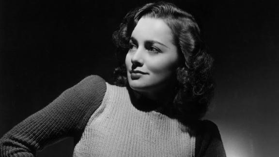 circa 1935:  Studio portrait of British-born actor Olivia de Havilland sitting on a stool and looking over her shoulder as she rests her hand on her hip.  De Havilland is wearing a long wool skirt and a knit sweater.  (Photo by Hulton Archive/Getty Images)