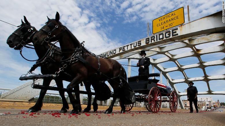 The casket of Rep. John Lewis moves over the Edmund Pettus Bridge by horse drawn carriage during a memorial service for Lewis on Sunday in Selma, Alabama.