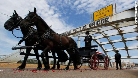 The coffin of the Rev. John Lewis moves across the Edmund Pettus Bridge on horses raised during a memorial service for Lewis on Sunday in Selma, Alabama.