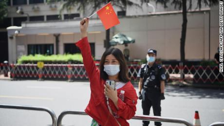 Uma mulher acena uma bandeira chinesa em frente ao consulado dos EUA em Chengdu, sudoeste da China.