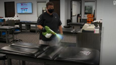 An Atlanta Falcons staff member uses an electrostatic sprayer to disinfect a training table.