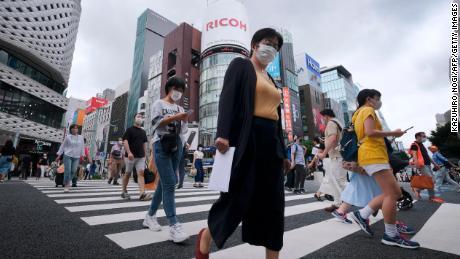 Des piétons marchent à un passage à niveau dans le quartier commerçant de Ginza à Tokyo le 25 juillet 2020.