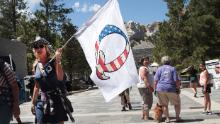 A Donald Trump supporter holding a QAnon flag visits Mount Rushmore National Monument in the US state of South Dakota on July 01, 2020.