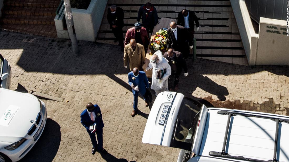 The casket of a coronavirus victim is carried from a funeral home in Johannesburg on July 26.