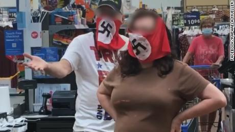 A couple has been banned from a Walmart after wearing swastika masks.