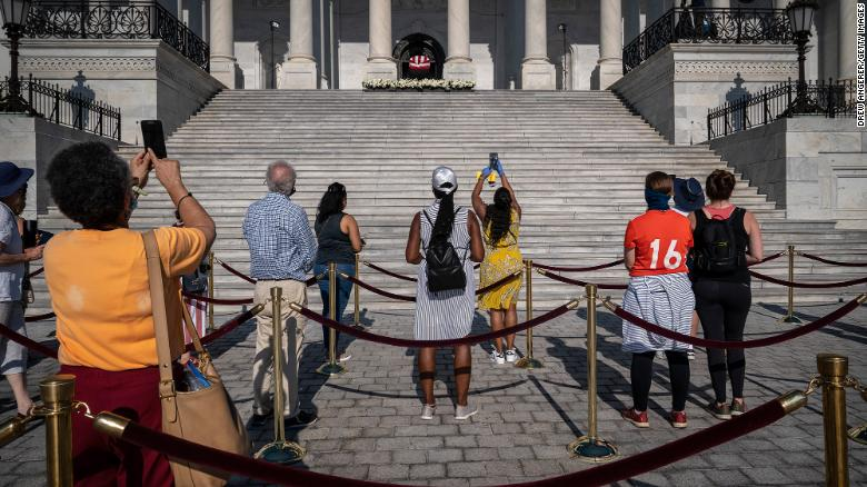 Members of the public view the casket of US Rep. John Lewis as he lies in state at the US Capitol on Tuesday, July 28. The public viewing is taking place outside because of the coronavirus pandemic.