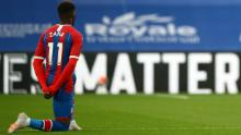 Wilfried Zaha takes a knee in support of the Black Lives Matter movement before the matcha against Burnley.