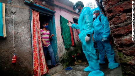 A medical worker who was wearing checked the temperature of a resident during a medical examination in a slum in Mumbai, India, on July 20, 2020.