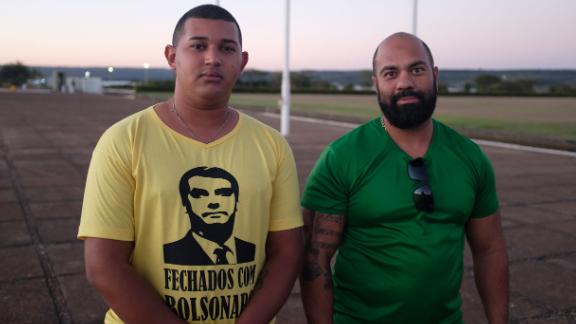 """Supporters of President Bolsonaro gather outside his residence. One wears a t-shirt that reads """"Sticking with Bolsonaro"""" on the front and """"All power to the people"""" on the back."""