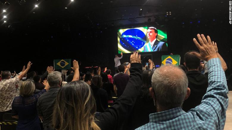 The congregation at Nucléo de Fé evangelical church prays for President Jair Bolsonaro.